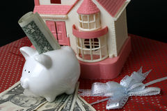 Saving for home. Piggy bank with dollars and home on top of a gift wrapped box concept for , saving for home as a gift Royalty Free Stock Photography
