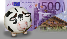 Saving for a house. This image shows a banknote of € 500 and a piggy bank and a house in the background. Shows the savings needed to purchase a home Royalty Free Stock Photos