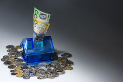 Saving for a house Money box. Blue Plastic house money box with $100 and $50 notes in the slot and coins spead out around. Copyspace Royalty Free Stock Image