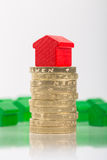 Saving for a house. A gred house on a pile of coins with green houses blurred in the background Royalty Free Stock Photo