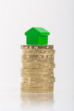 Saving for a house. A green house on a pile of coins Stock Photo