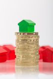 Saving for a house. A green house on a pile of coins with red houses blurred in the background Royalty Free Stock Images