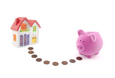 Saving for a house. Piggy bank with coins and house miniature Stock Image