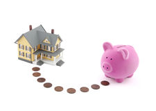 Saving for a house. Piggy bank with coins and house miniature Royalty Free Stock Images