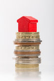 Saving for a house. A red house on a pile of coins Stock Photos
