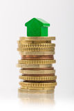 Saving for a house. A red house on a pile of coins Stock Photo
