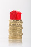 Saving for a house. A red house on a pile of coins Royalty Free Stock Photography