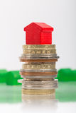 Saving for a house. A red house on a pile of coins with green house blurred in the background Royalty Free Stock Images