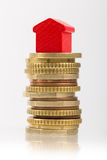 Saving for a house. A red house on a pile of euro coins Royalty Free Stock Photography