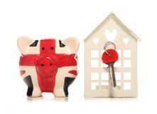 Saving for a house in the UK. Piggy bank on a white background Royalty Free Stock Images