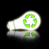 Saving Lamp. With green recycling symbol over black background with reflection Royalty Free Stock Photos