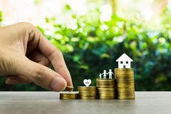 Saving or making money for family life in future concept. A man hand putting coin into rising stack of coins with heart, family. And small house model on wood royalty free stock photography
