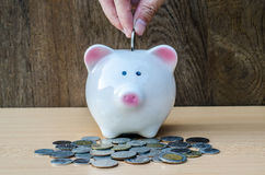 Saving, male hand putting a coin into piggy bank and money Royalty Free Stock Photography