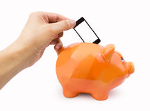 Saving with the mobile fee. Hand putting the cellphone into the piggy bank as concept saving with mobile fee stock photos
