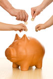 Saving money. Hands of different generations putting coins in piggy bank - saving money concept stock images