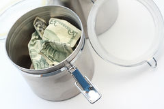 Saving Money. Save your money - store it.  Steel storage container with money in it Royalty Free Stock Images