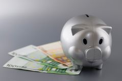 Saving money. A piggy bank on bills stock image