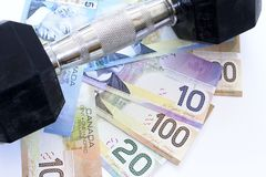 Saving Money. Canadian money with a weight resting  on top Stock Photography