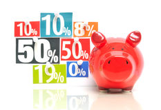 Saving money. Red piggy bank with multicolored newspaper percentage adverts Royalty Free Stock Photo