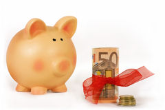 Saving money. Piggy bank and bankroll with a red ribbon isolated in white background Royalty Free Stock Photo