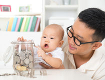 Saving money. Asian family lifestyle at home. Father and child saving coins to money jar, financial planning concept royalty free stock photography