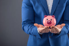 Saving money. Businesman holding pink piggy  and putting coin into piggy bank.  Stock Images