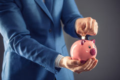 Saving money. Businesman holding pink piggy  and putting coin into piggy bank.  Stock Photo