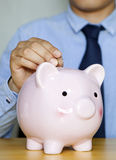 Saving money. Businessman saving money in a piggy-bank - isolated stock image
