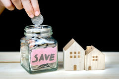 Saving money for buying house. Hand putting coin in glass jar of coin for saving money for buying house Royalty Free Stock Image