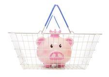 Saving money buying online. Piggy bank in a shopping basket cutout Royalty Free Stock Image