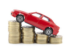 Saving money for a car. Toy car and coins over white