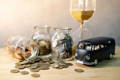 Saving money for car buying. Auto loan concept. Black car model with coin in currency glass jar and hourglass on wooden table. Car loan interest rate. Saving royalty free stock photo