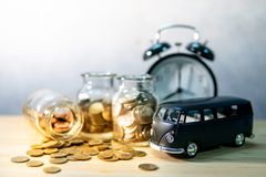 Saving money for car buying. Auto loan concept. Black car model with gold coin in currency glass jar and clock on wooden table. Car loan interest rate. Saving stock photo