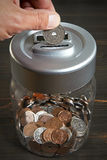 Saving money in a coin jar Royalty Free Stock Photography