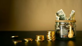 Saving money coin in jar. Symbol of investing, keeping money concept. Collecting cash banknotes in glass tin as moneybox. American dollars close-up with stock footage