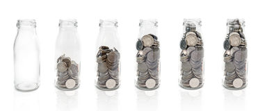 Saving money concept of collecting coins in glass bottle  from e Royalty Free Stock Photography