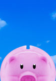 Saving Money Concept with Copy Space. Financial, saving money concept, pink piggy bank on blue sky background with copy space royalty free stock image