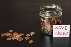 Saving money concept. Glass jar full of coins and sign save now. On black background stock images