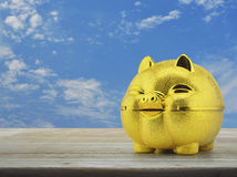 Saving money concept. Gold piggy bank on wooden table over blue sky with white clouds, Saving money concept royalty free stock image