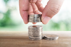 Saving money concept. hand putting coin to stacks of coins. Royalty Free Stock Photos