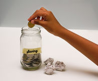 Saving Money Concept With Hand Putting A Coins On Glass Jar.Selective Focus And Shallow DOF. Saving Money Concept With Hand Putting A Coins Royalty Free Stock Photos