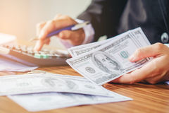 Saving money concept Man hand Holding Dollar bills and coin Writ Stock Images