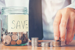 Saving money concept Man hand putting Row and coin Write Finance Royalty Free Stock Photography