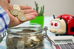 Man Dropping Coins Into Glass Jar. Saving money concept. A man`s hand is throwing coins into a glass jar Royalty Free Stock Image