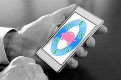 Saving money concept on a smartphone. Hand holding a smartphone with saving money concept royalty free stock image