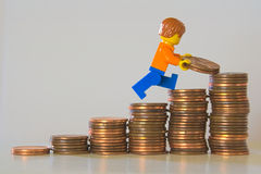 Saving money. Money saving concept - A toy figurine carrying coins up a stack of coins Royalty Free Stock Photos