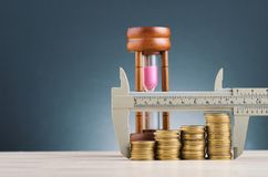 Vernier caliper and stacking coins on wooden desk over beautiful reverberation gradient background. Saving money concept,vernier caliper and stacking coins on stock photo