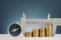 ,vernier caliper and stacking coins on wooden desk over beautiful reverberation gradient background. Saving money concept,vernier caliper and stacking coins on stock photography