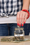 Saving money for education. Young woman putting coin into a jar. She is saving money for better education Stock Image