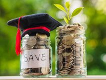 Saving money for education concept. Coins in glass jar with grad. Uate hat on blur background Stock Photography